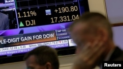 Traders work on the floor as a screen displays the Dow Jones Industrial average just after the opening bell at the New York Stock Exchange (NYSE) in New York City, New York, U.S. June 28, 2016.