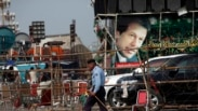 """A policeman walks past a campaign truck of Imran Khan, Chairman of the Pakistan Tehreek-e-Insaf (PTI) political party, during what has been dubbed a """"freedom march"""" in Islamabad August 22, 2014. Khan, who has been leading protesters trying to bring down P"""