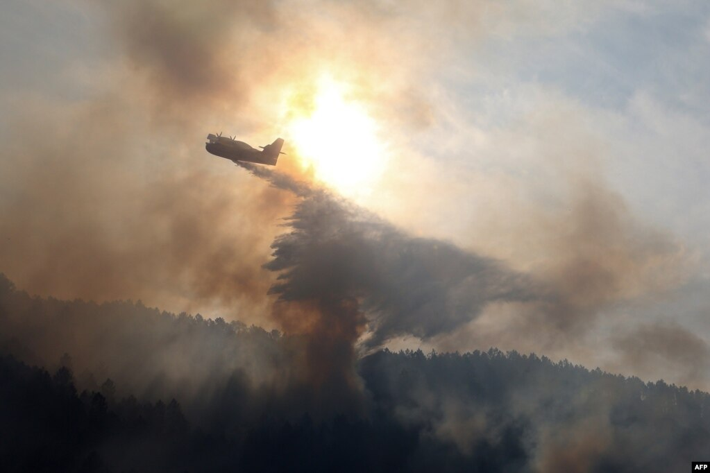 A canadair bomber plane drops water onto a fire along the l'Arone Pass in the Bavella mountains in Quenza on the French Mediterranean island of Corsica. Strong winds from storm Ciara caused wildfires to spread on the island.