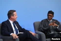 Nigerian President Muhammadu Buhari listens as British Prime Minister Cameron opens the international anti-corruption summit on May 12, 2016 in London, England.