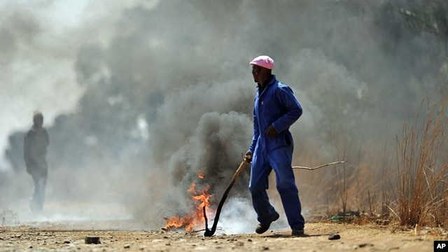 In this photo taken Monday, Sept 3, 2012, sacked gold miners set up a burning barracade at Gold One International's mine east of Johannesburg.