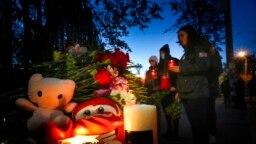 Para mahasiswa menyalakan lilin di antara karangan bunga dan foto-foto korban di luar kampus Universitas Negeri Perm, Rusia, pada 21 September 2021. Tujuh orang tewas dalam peristiwa penembakan di kampus tersebut yang terjaid pada Senin (20/9). (Foto: AP/Dmitri Lovetsky)