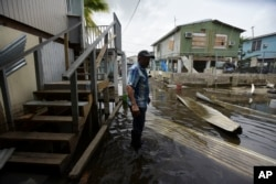 Juana Matos resident Hector Rosa walks through a flooded area after the passing of Hurricane Maria, in Puerto Rico, Wednesday, September 27, 2017.