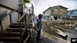 Juana Matos resident Hector Rosa walks through a flooded area after the passing of Hurricane Maria, in Puerto Rico, Wednesday, September 27, 2017. Since the devastating impact of said hurricane, the supply line of goods in general was interrupted in the US territory, causing endless rows in gas stations and comercial centers.