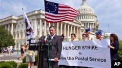 Ohio representative Dennis Kucinich and activists from the Postal Workers Union demonstrate to urge Congress to take action to help the United States Postal Service in June.