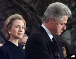 FILE - Then first lady Hillary Clinton watches her husband, President Bill Clinton, pause as he thanks those Democratic members of the House of Representatives who voted against his impeachment, Dec. 19, 1998. Clinton was impeached by the House but later aquitted in the Senate.