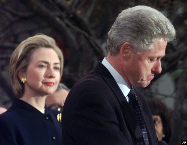 FILE - Then-first lady Hillary Clinton watches her husband, President Bill Clinton, pause as he thanks those Democratic members of the House of Representatives who voted against his impeachment, Dec. 19, 1998.