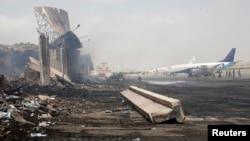 Beberapa unit pesawat terbang terlihat berada di dekat bangunan yang hancur di Bandara Internasional Jinnah pasca serangan militer Taliban di Karachi, Pakistan (10/6).