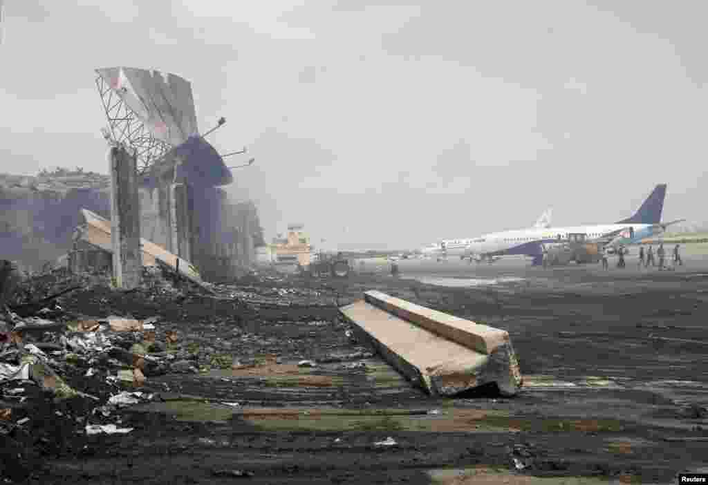 Planes are seen near a section of a damaged building at Jinnah International Airport, after Sunday's attack by Taliban militants, Karachi, Pakistan, June 10, 2014.