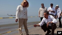 President Barack Obama and Lafourche Parish President Charlotte Randolf, left, inspect a tar ball as they look at the effect the BP oil spill is having on Fourchon Beach in Port Fourchon, Louisiana, May 28, 2010. (Official White House Photo by Chuck Kenne
