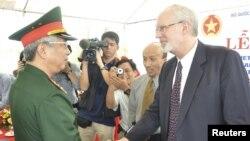 Wakil Menteri Pertahanan Vietnam Nguyen Chi Vinh (kiri) berjabat tangan dengan Dubes Vietnam David Shear dalam upacara peresmian kerjasama AS-Vietnam untuk pembersihan sisa pencemaran akibat Dioxin di Vietnam (9/8).