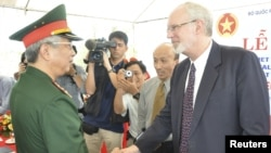 越南和美國官員在峴港啟動清除橙劑項目儀式上握手