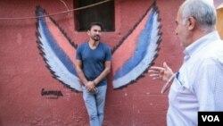 Ayad Nasser (kiri) berbicara dengan warga setempat. (J. Owens for VOA)