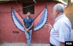 Ayad Nasser (left), talks to a local resident. Born in Ouzai in 1970, he has returned to the neighbourhood with artists and volunteers. (J. Owens for VOA)