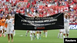 Jun 27, 2015; Vancouver, British Columbia, CAN; England midfielder Fara Williams (4) and midfielder Katie Chapman (16) raise a banner for Canada after the quarterfinals of the FIFA 2015 Women's World Cup at BC Place Stadium. England won 2-1. Mandatory Cre