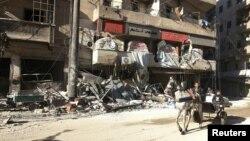 Warga mengendarai kereta kuda di dekat bangunan rumah sakit al-Hakeem di Aleppo, Suriah yang hancur akibat serangan udara (19/11).