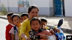 Женщина-уйгурка и ученики уйгурской школы. Синцзян-Уйгурский автономный район КНР (архивное фото)