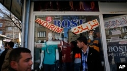 FILE - In this March 19, 2017 photo, Syrian refugees walk past stores with signs in Arabic and Turkish, in Gaziantep, southeastern Turkey.
