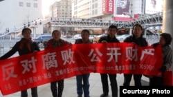 Para aktivis melakukan unjuk rasa anti korupsi dengan membawa spanduk di Beijing (9/4).