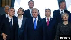 From left, NATO Secretary General Jens Stoltenberg, Greek Prime Minister Alexis Tsipras, U.S. President Donald Trump, Hungarian Prime Minister Voktor Orban and Britain's Prime Minister Theresa May pose for a family photo during a NATO summit at their new