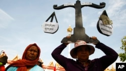 A protester from Boeung Kak lake holds a cutout of a scale symbolizing justice as she joins other villagers, who were allegedly evicted from their homes without adequate compensation, during a rally in front of the Justice Ministry in Phnom Penh, Cambodia, file photo.