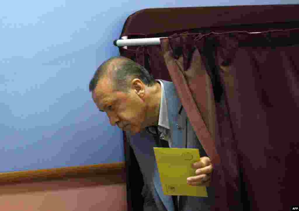 Turkey's Prime Minister Tayyip Erdogan gets ready to cast his vote at a polling station in Istanbul June 12, 2011. Turks began voting in an election on Sunday that is expected to return Prime Minister Tayyip Erdogan to office for a third consecutive term
