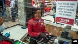 Zandile Mlotshwa, 21 ans, caissière au supermarché Spar dans la banlieue de Norwood à Johannesburg, compte son argent à la fin de sa journée de travail le 30 mars 2020. (AP Photo/Jerome Delay)