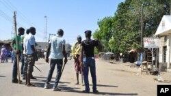 1일 나이지리아 보르노주 마이두구리시에서 두 건의 폭탄테러가 발생한 후 자경단원들이 도로를 차단하고 있다.