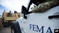 FILE - Department of Homeland Security personnel deliver supplies to Santa Ana community residents in the aftermath of Hurricane Maria in Guayama, Puerto Rico, Thursday, Oct. 5, 2017.