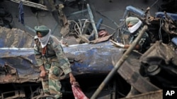 Indian army personnel pull out the body of a victim from the wreckage of a Kalka Mail passenger train that derailed near Fatehpur in Uttar Pradesh state, India, July 11, 2011