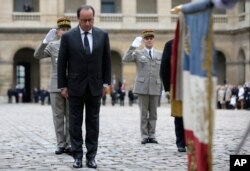 French President Francois Hollande attends a military ceremony in the courtyard of the Hotel National des Invalides, in Paris, Nov. 19, 2015.