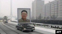 Cenaze kortejinin önünde Kim Jong İl'in dev bir portresi taşındı