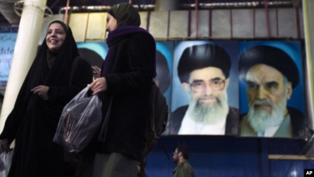 Iranian women walk in front of the pictures of Ayatollah Ruhollah Khomeini, the founder of the Islamic Republic (R) and Iran's Supreme Leader Ayatollah Ali Khamenei during the anniversary ceremony of Iran's Islamic Revolution at the Behesht Zahra cemetery