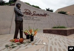Flowers lay alongside a basketball fans have left at the Pat Summitt statue in Knoxville, Tennessee, June 28, 2016.