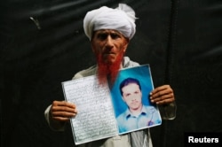 Shodeen Khan 77, holds a photo of his son, Mustaqeem Khan, a former student of the Islamia College Peshawar who has been missing for nine years, is seen at a human rights rally by the Pashtun Tahaffuz Movement (PTM), in Karachi, Pakistan, May 13, 2018.