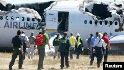 Para penyelidik dari Badan Keamanan Transportasi Nasional Amerika (NTSB) di lokasi kecelakaan pesawat Asiana Airlines Flight 214 di Bandar Udara San Francisco, Juli 2013.