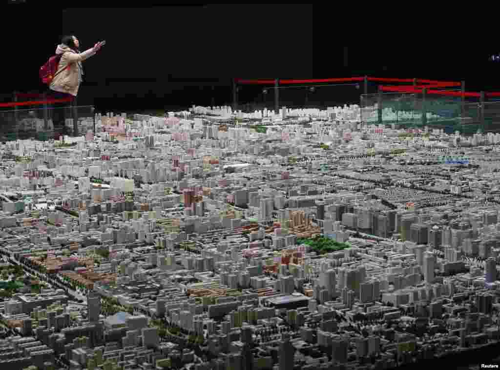 Seorang pengunjung mengambil foto sebuah model kota Beijing yang dipamerkan di sebuah museum di Beijing, China.