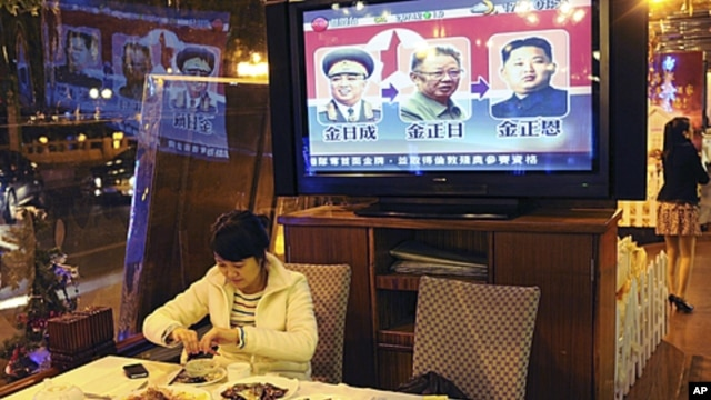 A woman eats a meal in a restaurant in Guangzhou, southern China Guangdong province while television reports on the successive North Korean leaders; from left Kim Il Sung, Kim Jong Il and Kim Jong Un, December 20, 2011.