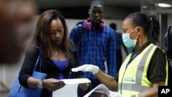 Petugas kesehatan Nigeria memberikan penjelasan kepada penumpang di bandara Lagos, Nigeria, Rabu (6/8).