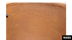 """NASA's Ingenuity Mars Helicopter took this color image during its fourth flight, on April 30, 2021. """"Airfield B,"""" its new landing site, can be seen below. The helicopter will seek to set down there on its fifth flight attempt. (NASA/JPL-Caltech)"""