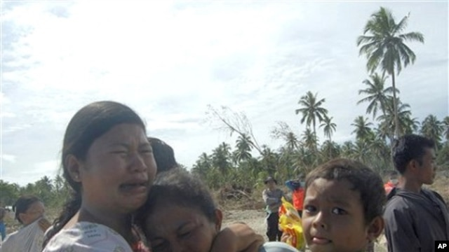 Tsunami survivors weep on ravaged Pagai island, in Mentawai Islands, Indonesia, 28 Oct. 2010.