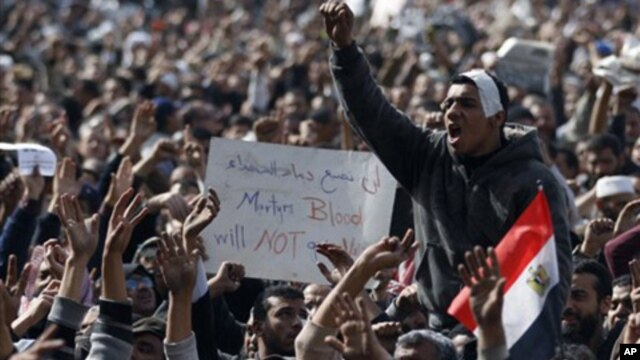 Anti-government protesters react in Tahrir Square, Cairo, Egypt, Friday, Feb. 4, 2011