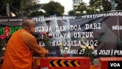 Seorang Banthe menaruh bunga untuk para ABK KRI Nanggala 402 yang gugur (foto Petrus Riski/VOA)
