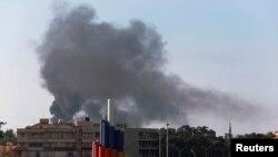 Asap mengepul akibat pertempuran pasukan pemerintah dan milisi Islamis di Benghazi, Libya (26/11).