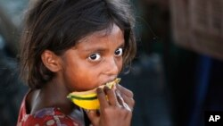 FILE - A child laborer eats a piece of a muskmelon on the World Day against Child Labor on the outskirts of Jammu, India, June 12, 2015.