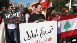 """Activists hold Lebanese flags and an Arabic placard, center, that reads: """"your extension is an occupation, no to the extension,"""" during a protest against the extension of the Lebanese parliament, on a road that leads to the Parliament building, in downtown Beirut, Nov. 5, 2014."""