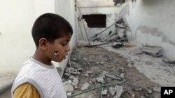 反对派控制的米苏拉塔一带仍然战火纷飞。图为一名男孩6月21日站立在据称被卡扎菲的军队轰炸过的房子里。