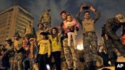 ບັນດາທະຫານກອງທັບບົກອີຈິບ ສະເຫຼີມສະຫຼອງ ພ້ອມກັບພວກລູກເຕົ້າຂອງເຂົາເຈົ້າ ຢູ່ເທິງລົດຫຸ້ມເກາະ ບັນທຸກທະຫານ, ໃນຂະນະທີ່ໄດ້ຍິນຂ່າວຄາວ ຂອງການລາອອກ ຈາກຕຳແໜ່ງຂອງປະທານາທິບໍດີ Hosni Mubarak ເມື່ອວັນທີ 11 ກຸມພາ 2011.