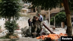 FILE - Members of the Islamist rebel group Jabhat al-Nusra prepare a homemade mortar in the Bustan al-Qasr neighborhood of Aleppo, Syria, June 5, 2014.