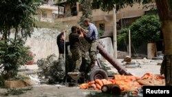 Thành viên của nhóm phiến quân Hồi giáo al-Nusra Front chuẩn bị súng cối tự chế trong khu vực Bustan al-Qasr của thành phố Aleppo, Syria.